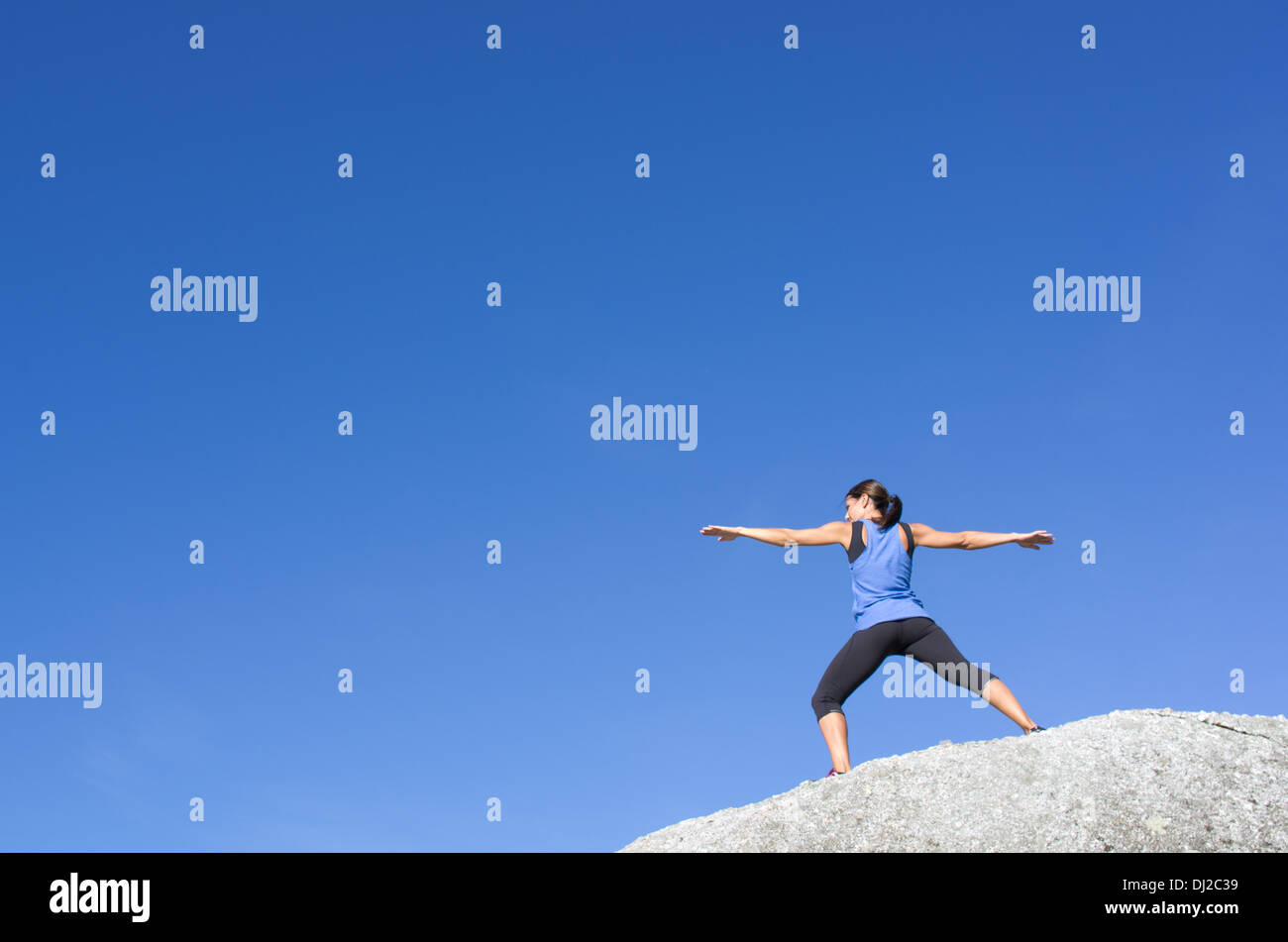 Warrior pose on a white rock against a perfectly blue sky. - Stock Image