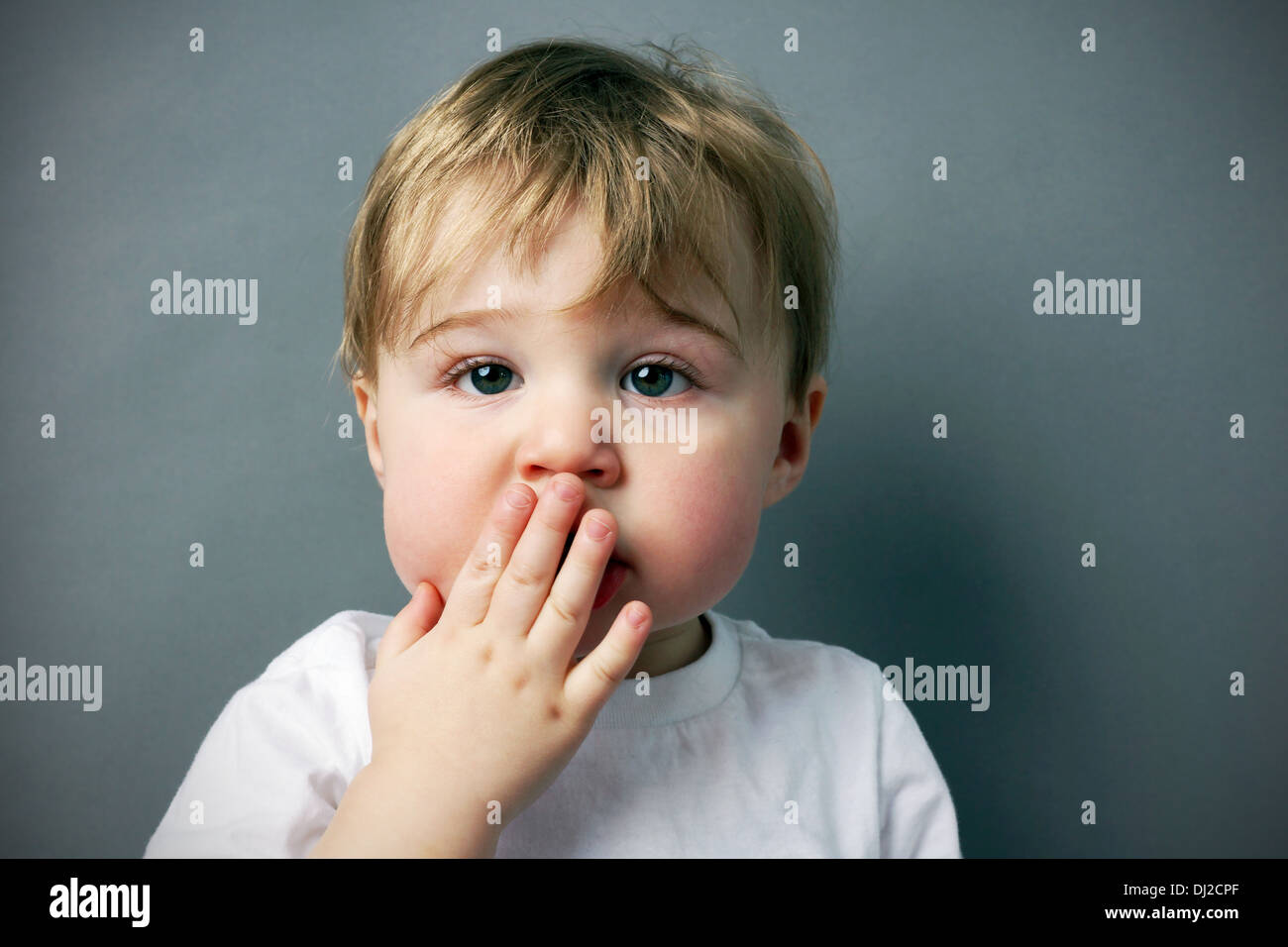 oops! cute and funny little blond boy or toddler with hand in front of mouth - Stock Image