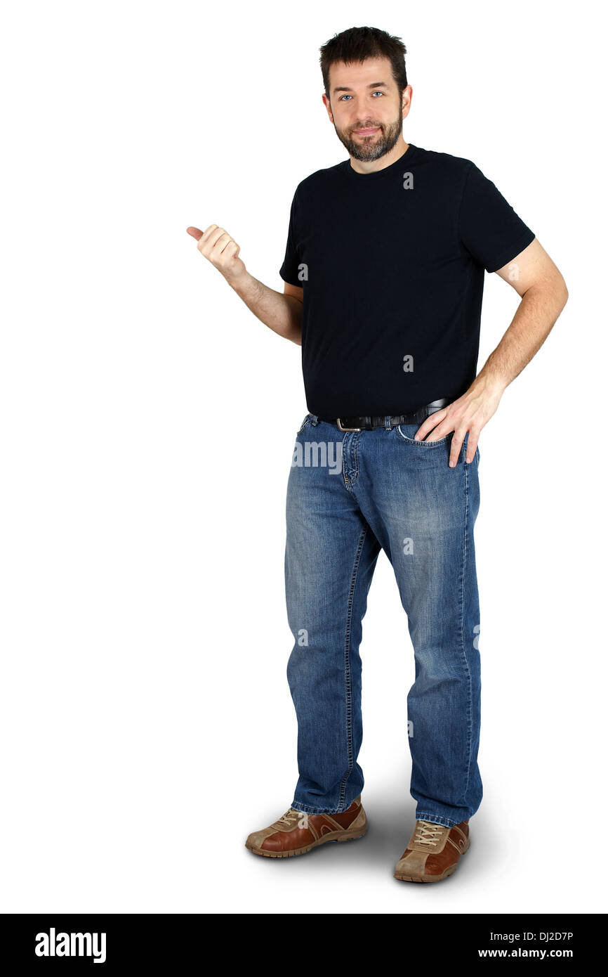 Complete body of ordinary guy or man pointing beside him and smiling, copy space. - Stock Image