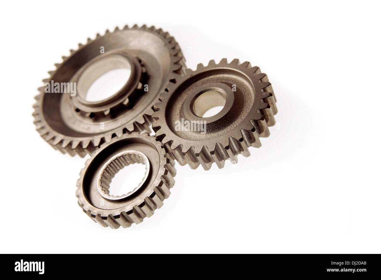 Metal cog gears joining together - Stock Image