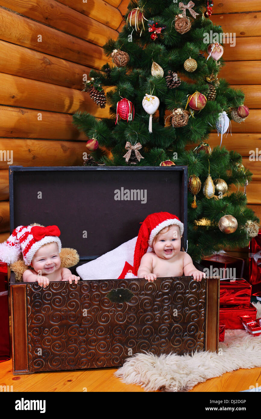 2f2d2dcb190a0 Two cute baby girls in xmas hats inside large chest - Stock Image