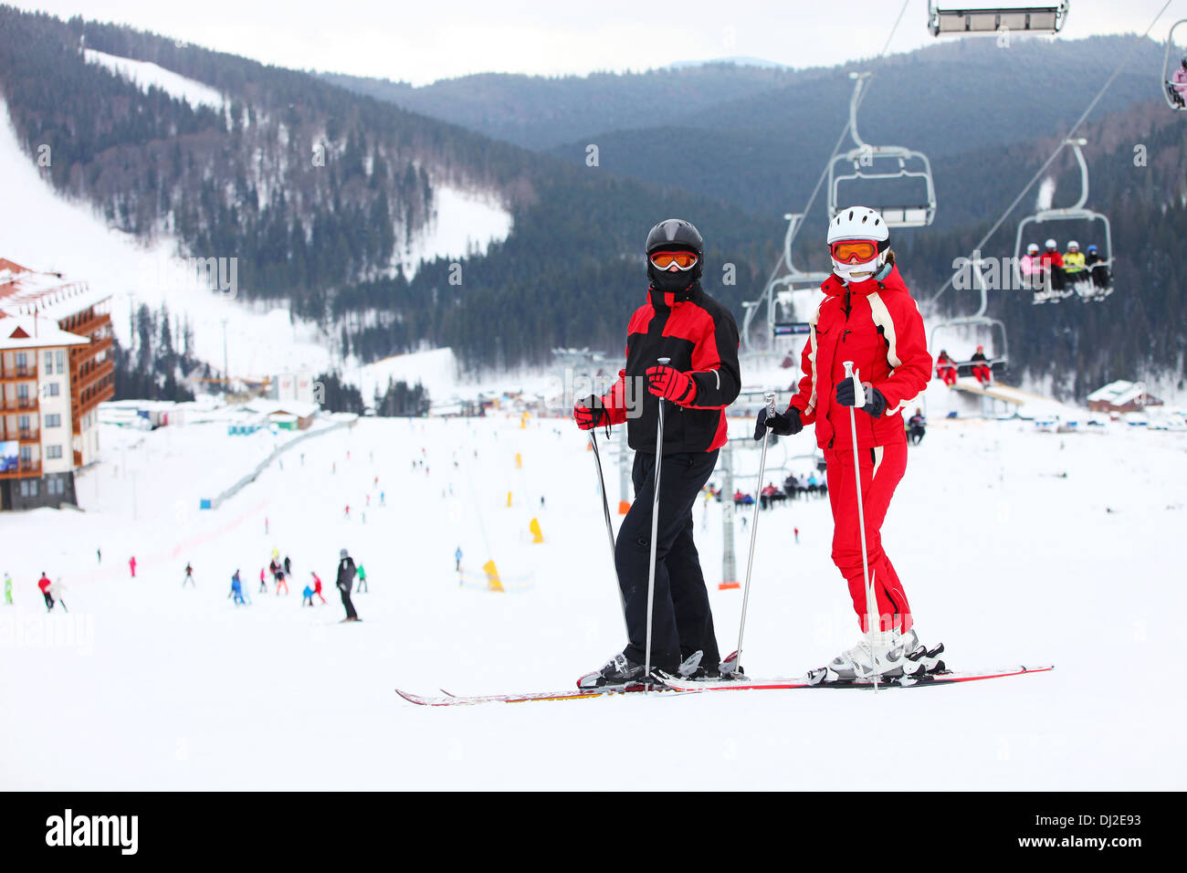 Young couple standing on a ski slope - Stock Image
