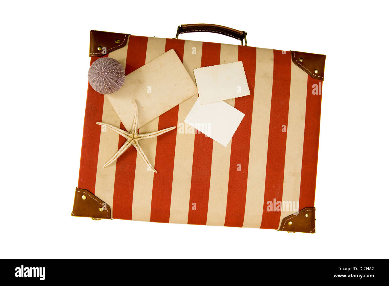 Old suitcase with blank photos and seashells isolated on white - Stock Image
