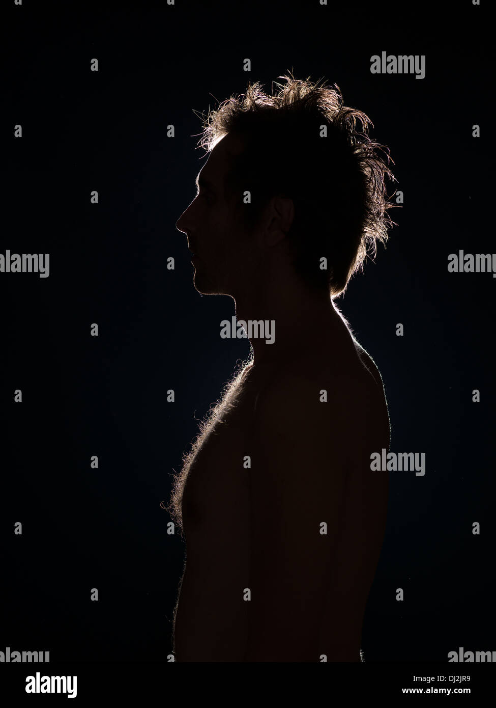 side view of man with back ligthing on black background - Stock Image