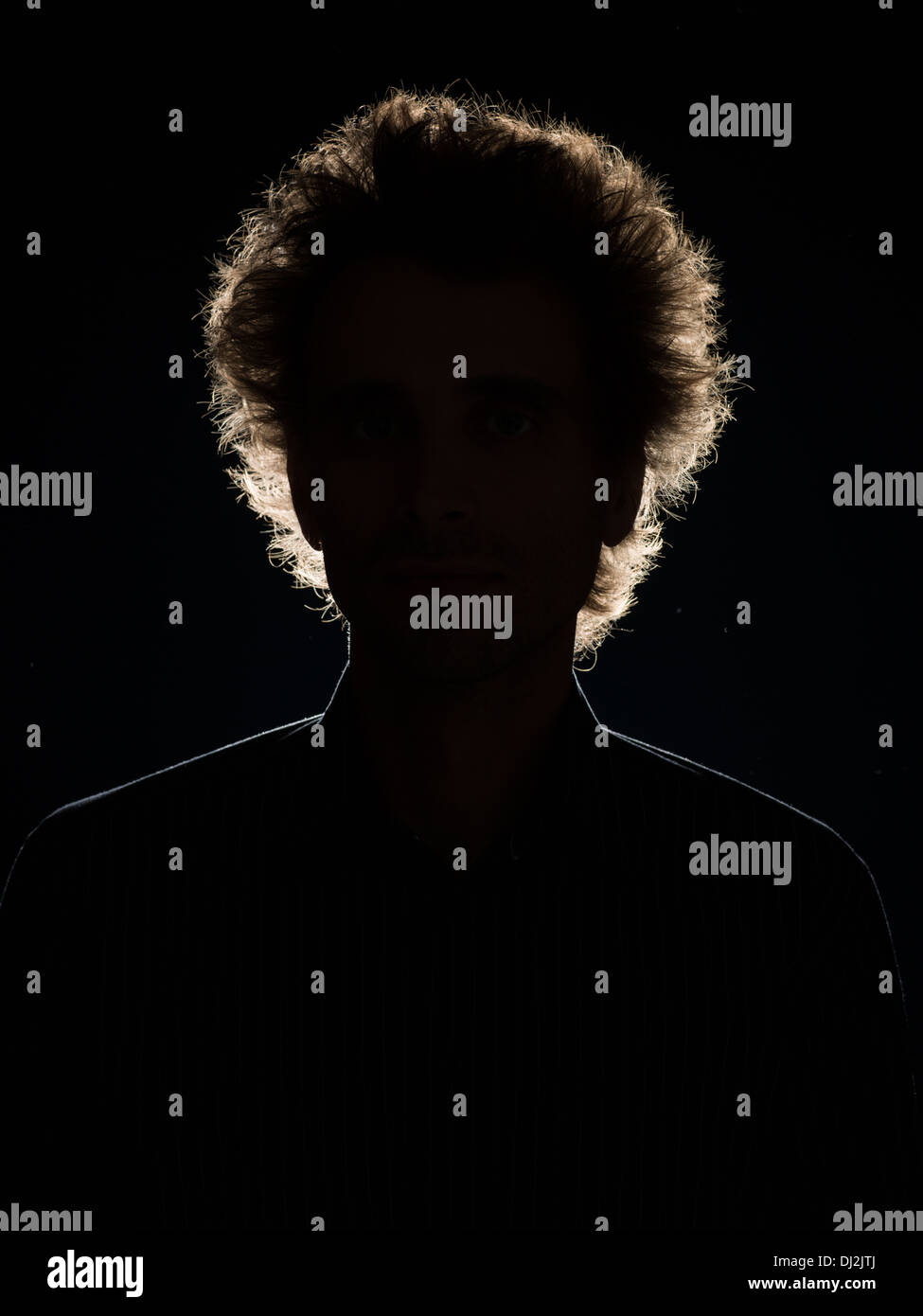 front view of man in shadow with back lighting on black background - Stock Image