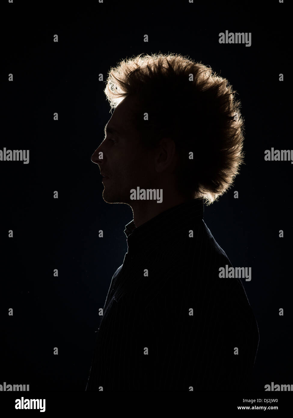 side view of man with back lighting on black background - Stock Image