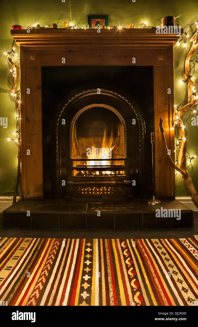 A warming, festive fireside with fairy lights and rug. - Stock Image