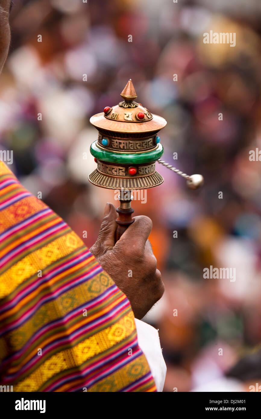 Bhutan, Thimpu Dzong, annual Tsechu, handoff old man spinning prayer wheel - Stock Image