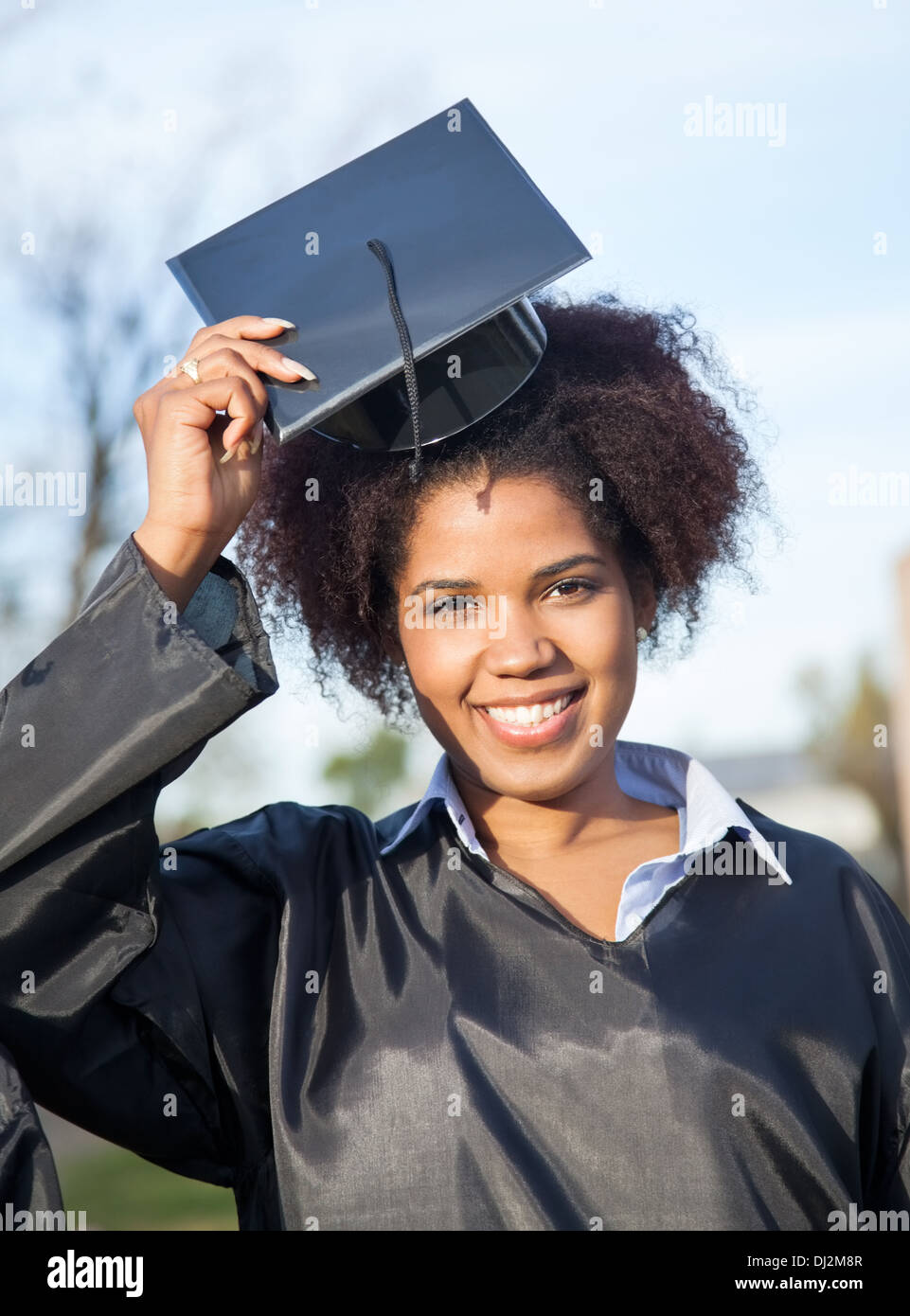 Woman In Graduation Gown Wearing Mortar Board On Campus Stock Photo ...