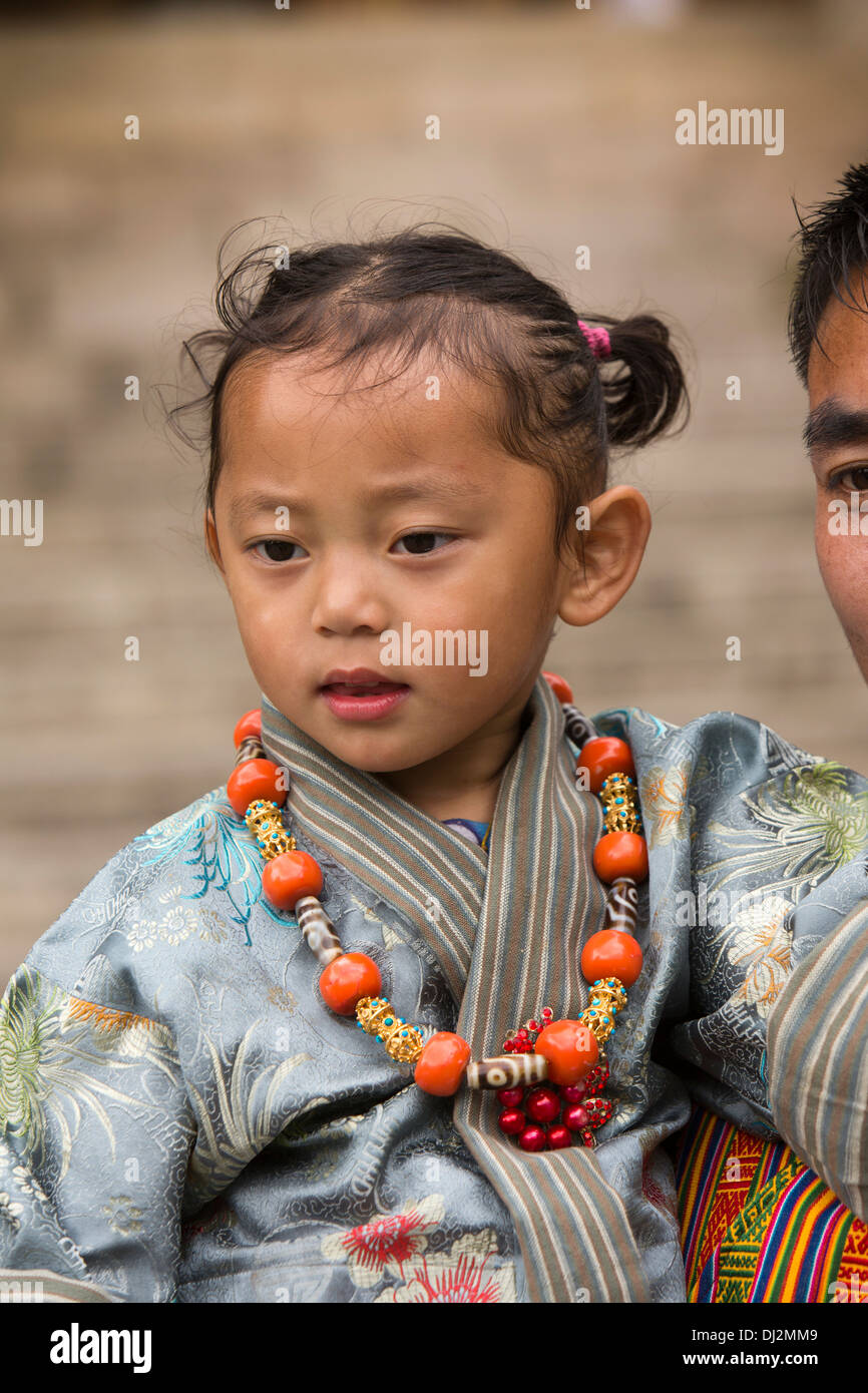 Bhutan, Thimpu Dzong, annual Tsechu, traditionally dressed young girl in father's arms - Stock Image