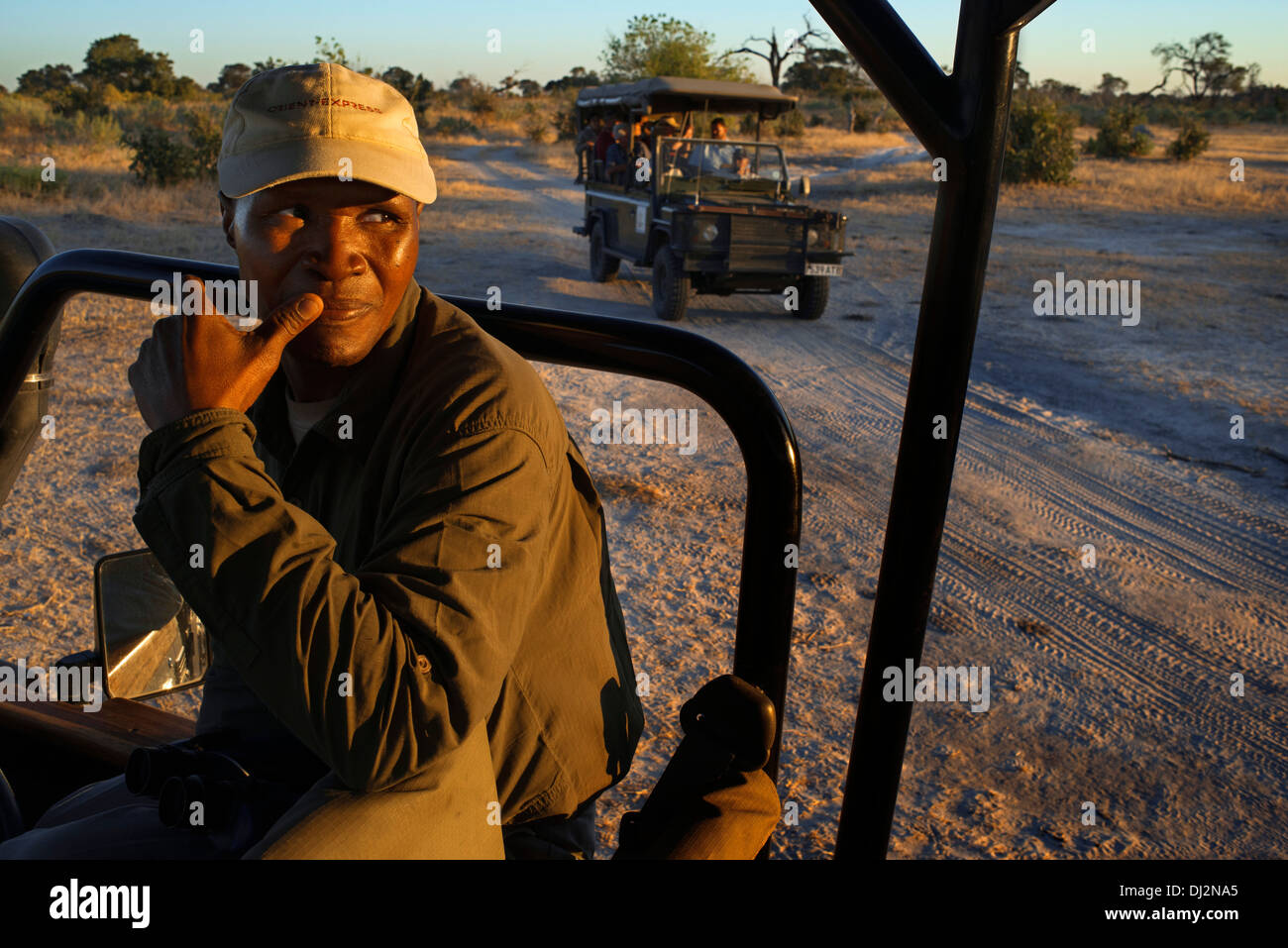 One of the guides Savute Elephant Camp by Orient Express in Botswana in the Chobe National Park . uploaded to one of the 4x4. - Stock Image