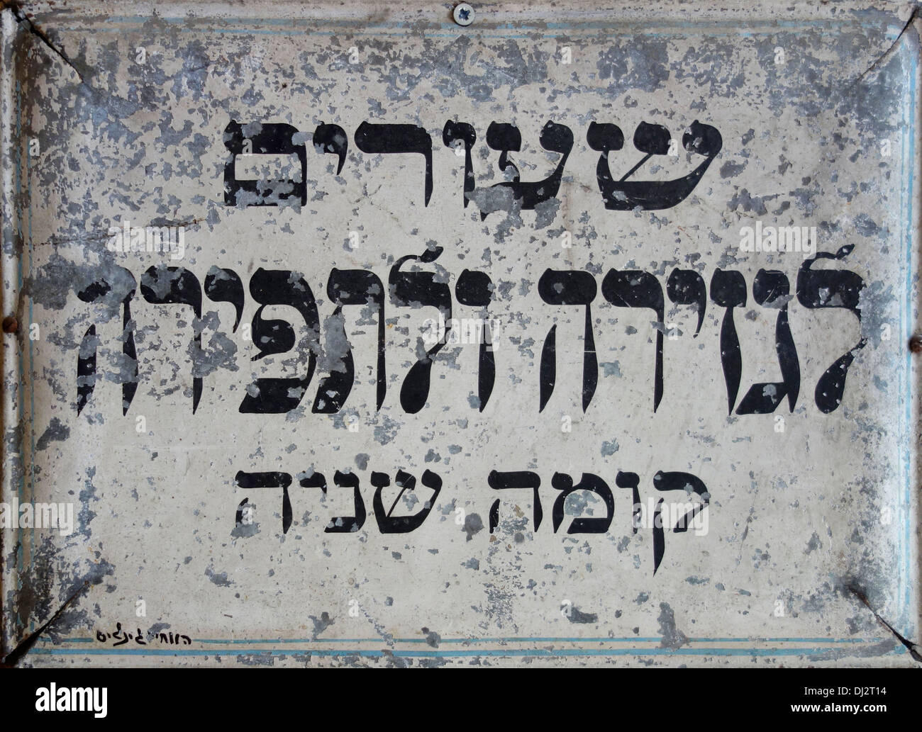 An old signboard in Hebrew which reads 'Lectures for Cutting and Sewing. Second Floor'  in Israel - Stock Image