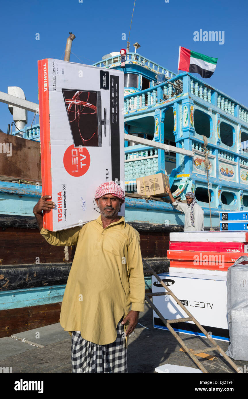 Men loading cargo onto dhows at cargo wharf on The Creek in Dubai United Arab Emirates - Stock Image