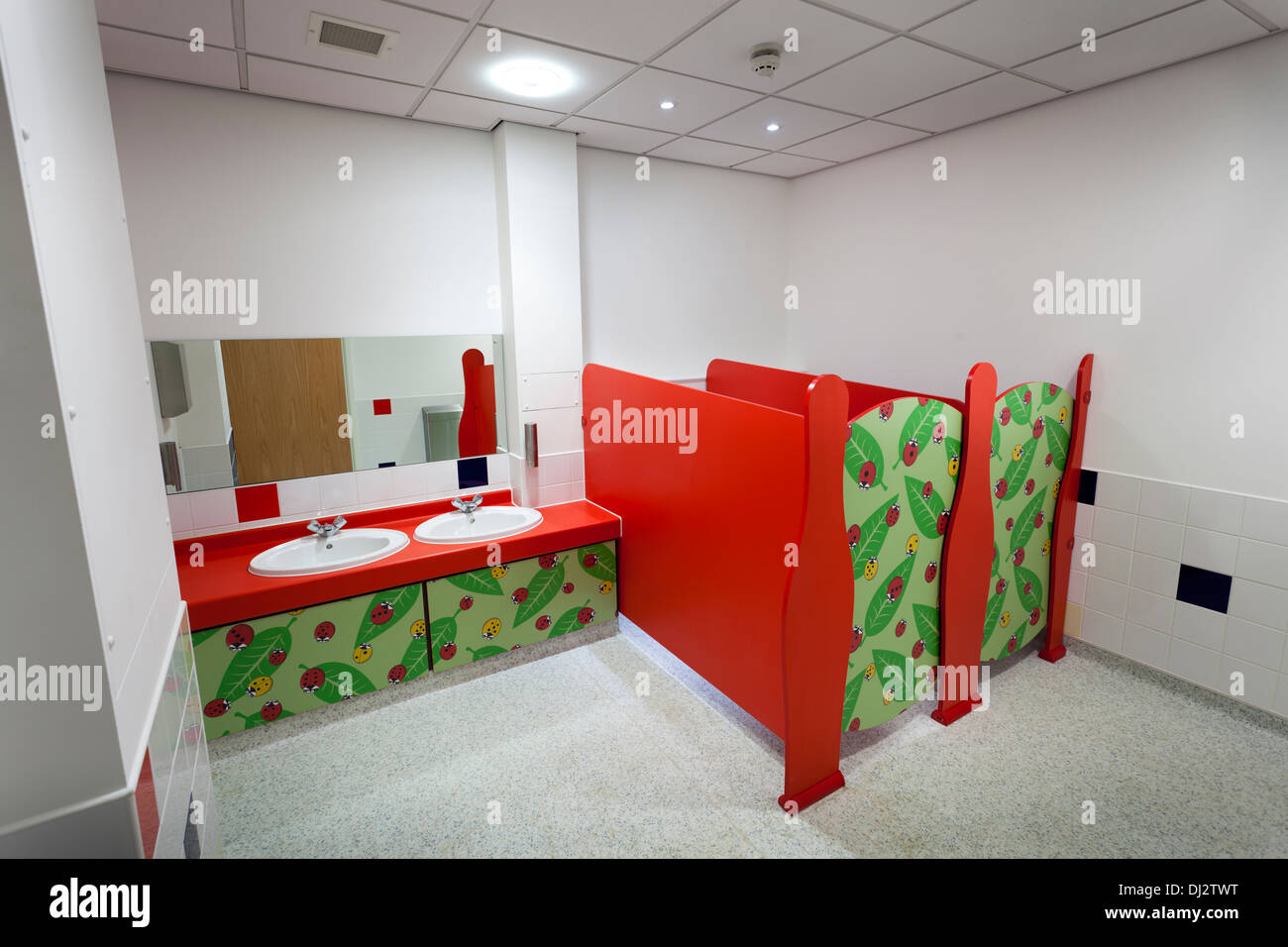 Colourful infants toilets with low walled cubicles and wash basins. - Stock Image