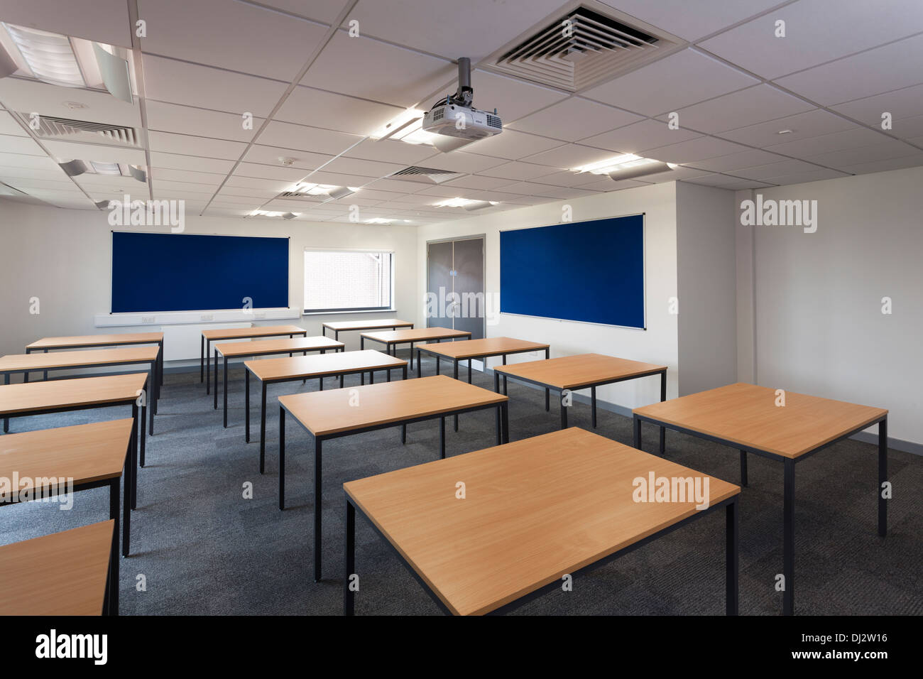 Empty new school classroom laid out with desk tables. - Stock Image