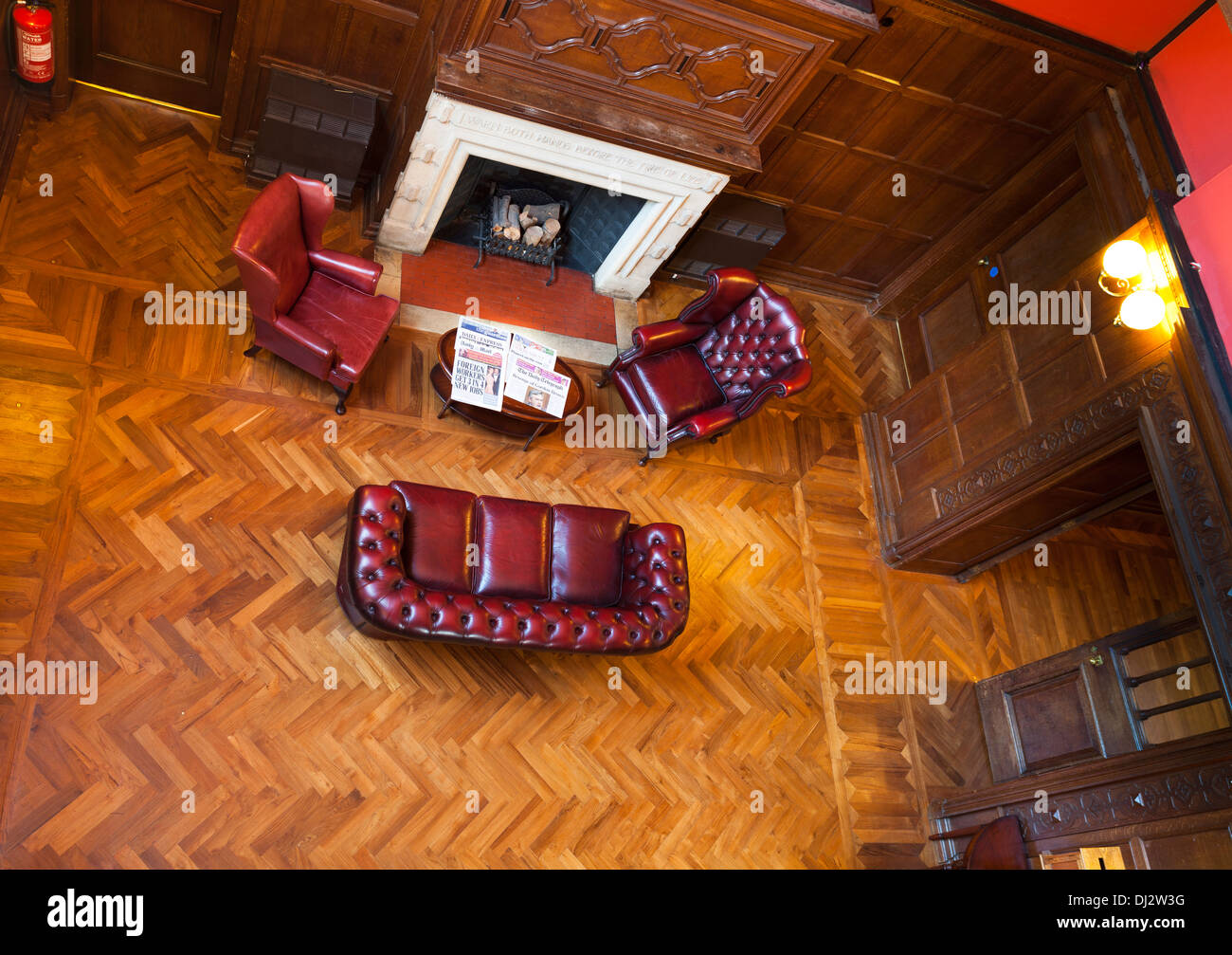 Looking down on hotel soft chairs and sofa with log fireplace and parquet flooring. - Stock Image