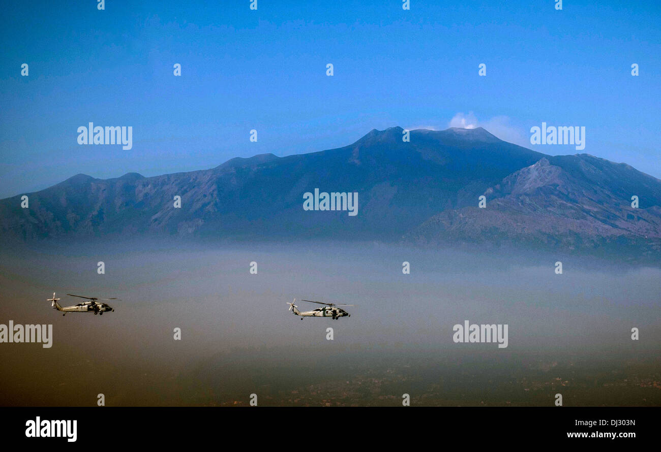 US Navy MH-60S Sea Hawk helicopters fly in formation past the alps October 29, 2013 off the coast of Naples, Italy. - Stock Image