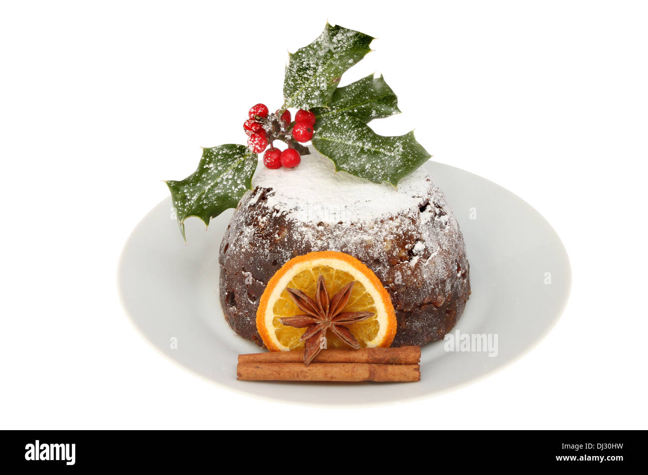 Christmas pudding on a plate decorated with holly, orange, cinnamon and star anise isolated against white - Stock Image