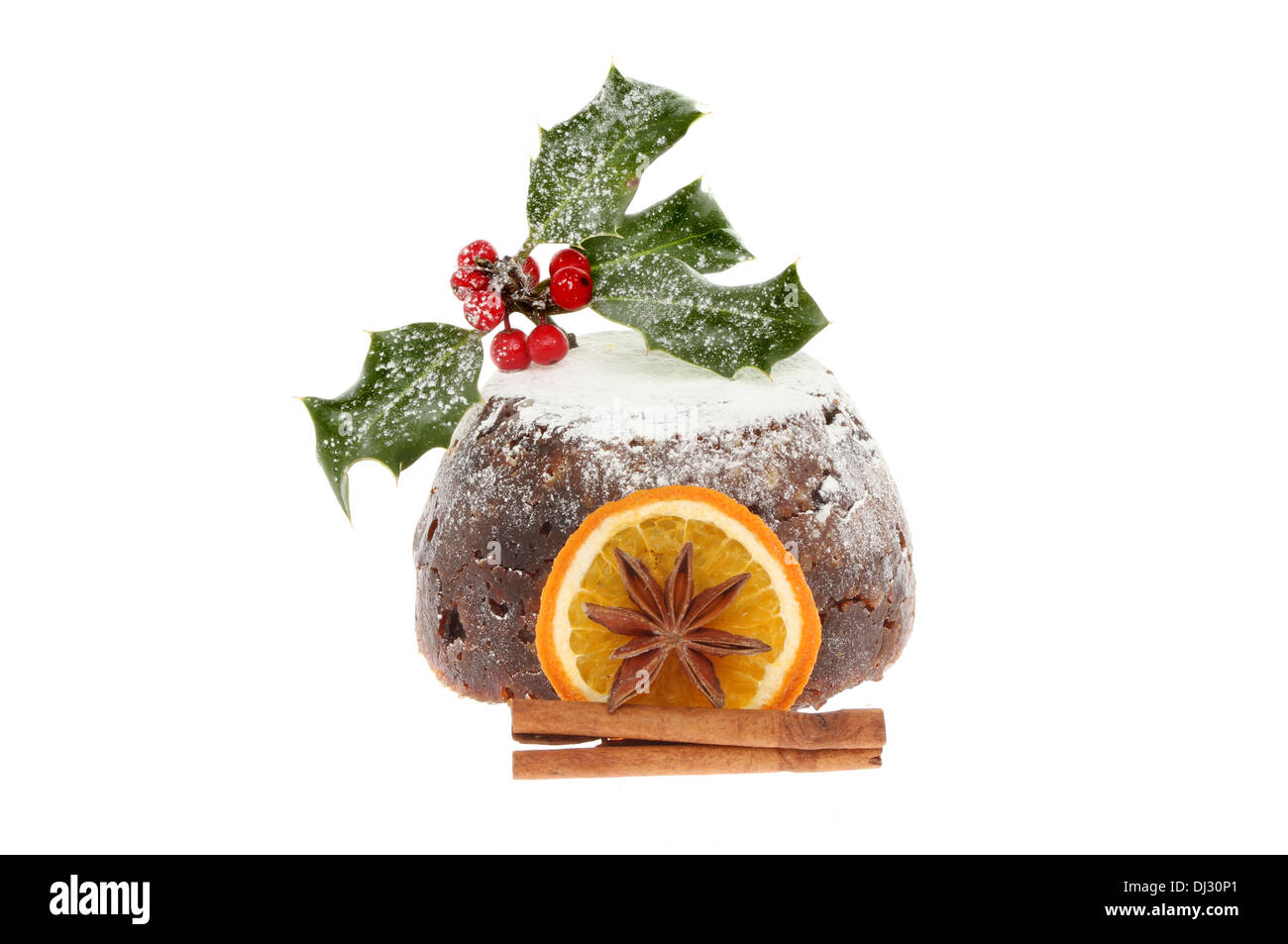 Christmas pudding dusted with icing sugar and decorated with spice and holly isolated against white - Stock Image