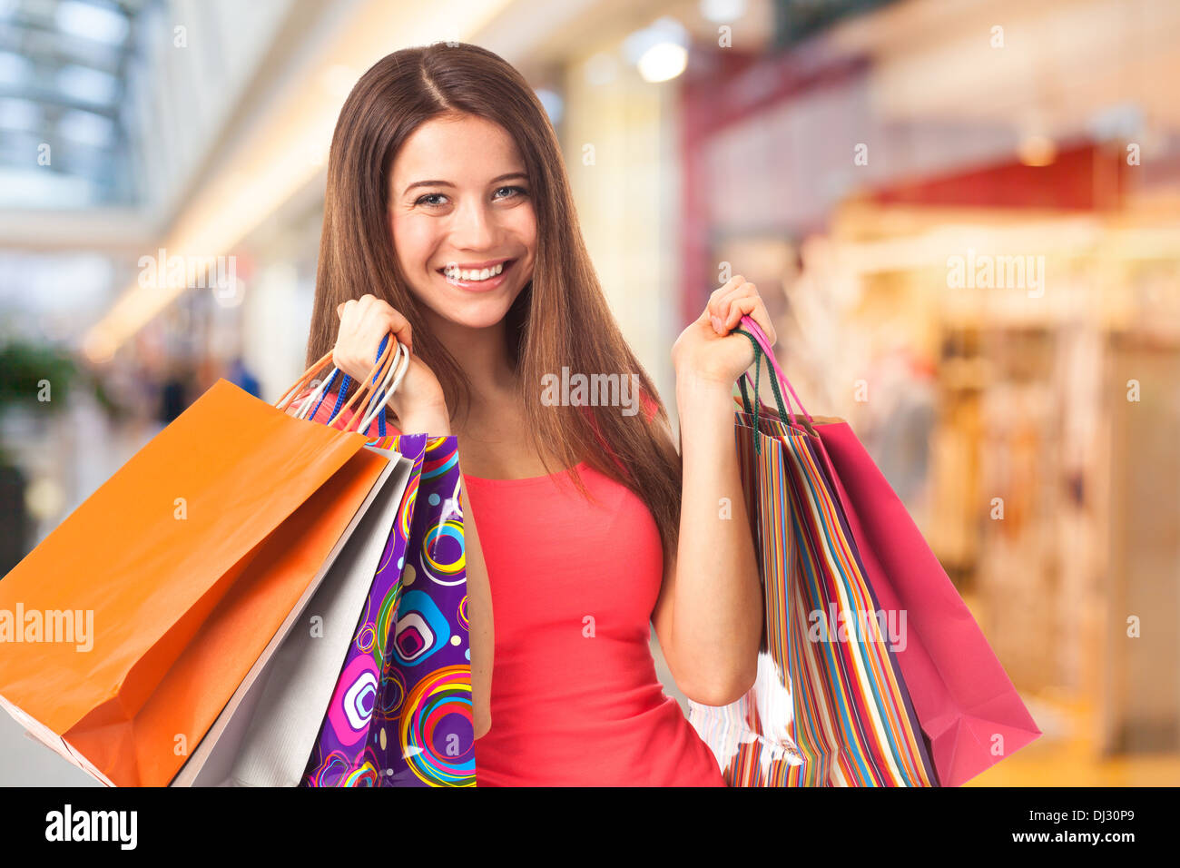 Portrait of a pretty young woman holding shopping bags in a supermarket - Stock Image