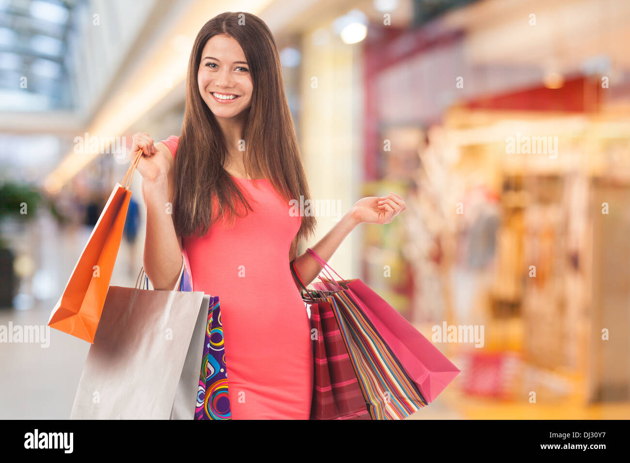 Portrait of a nice young woman holding shopping bags - Stock Image