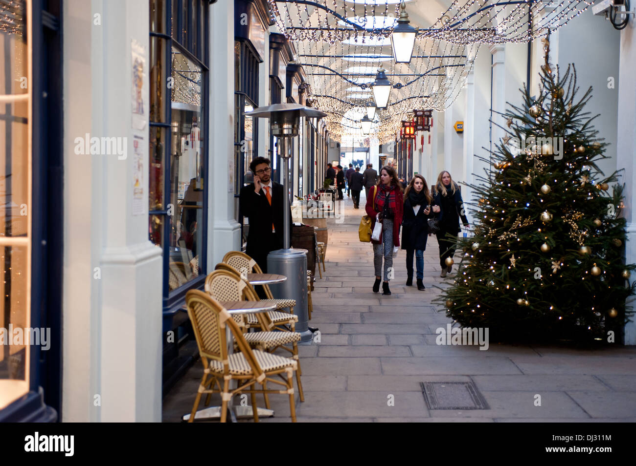 London, UK - November 19, 2013:People stroll in the Royal Opera Arcade, the first covered shopping street in Britain - Stock Image