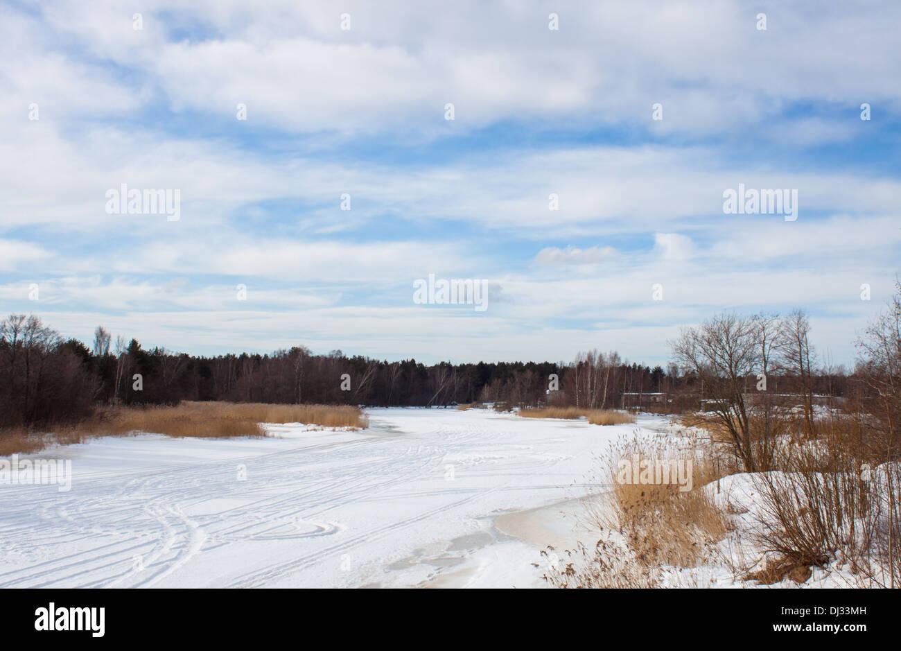 'snowy river' 'frozen river'  winter landscape snow 'ski run' forest blue sky clouds nature - Stock Image