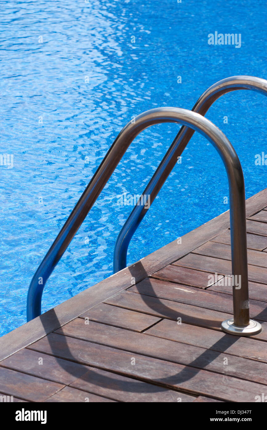 Ladder and handrail on the banks of a swimming pool - Stock Image