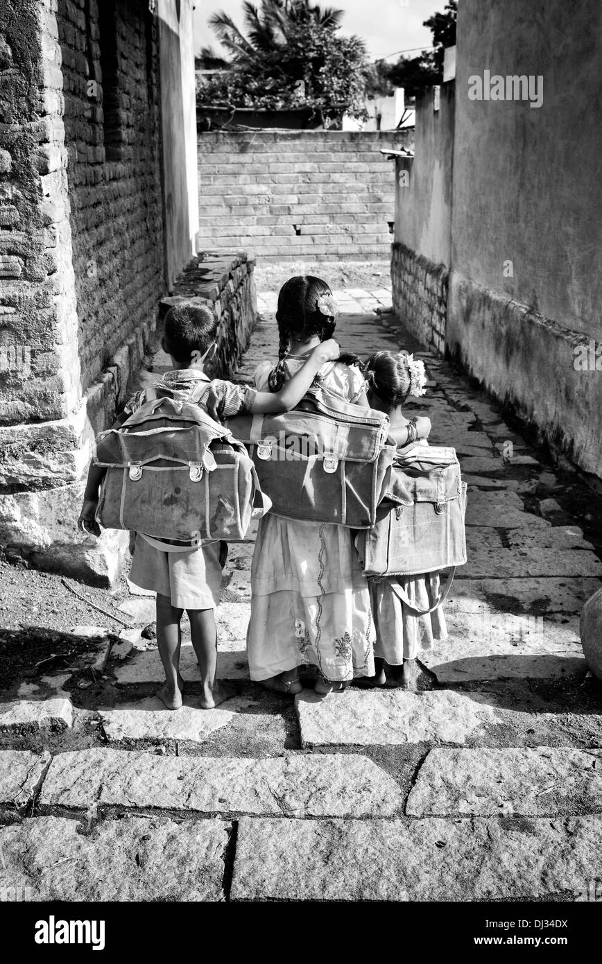 Three small indian children going to school in a rural indian village andhra pradesh