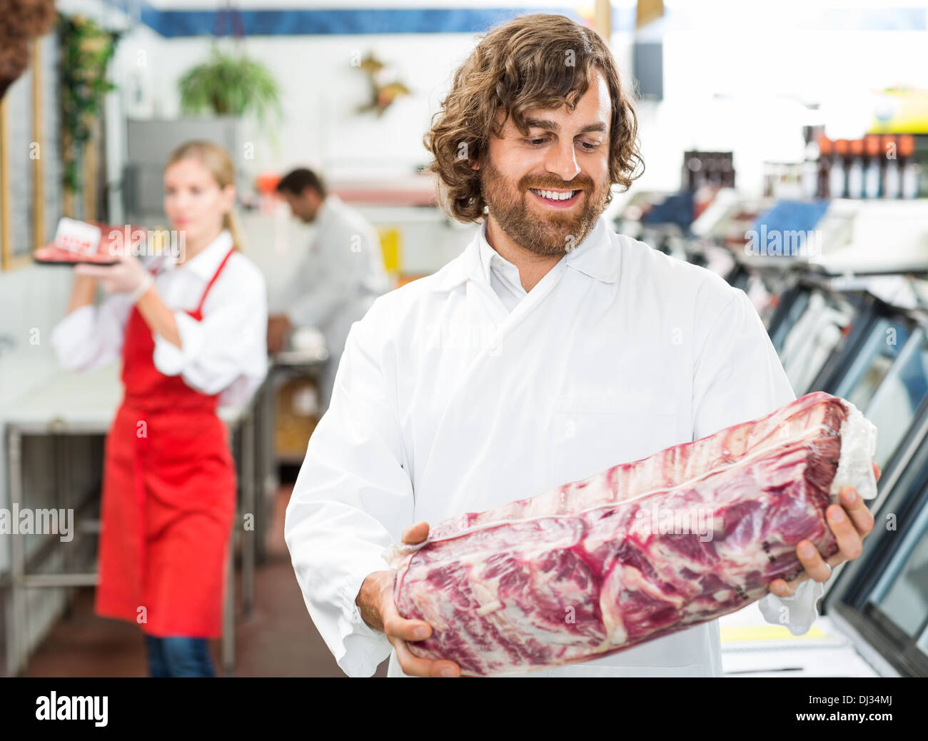 Happy Butcher Looking At Meat Package - Stock Image