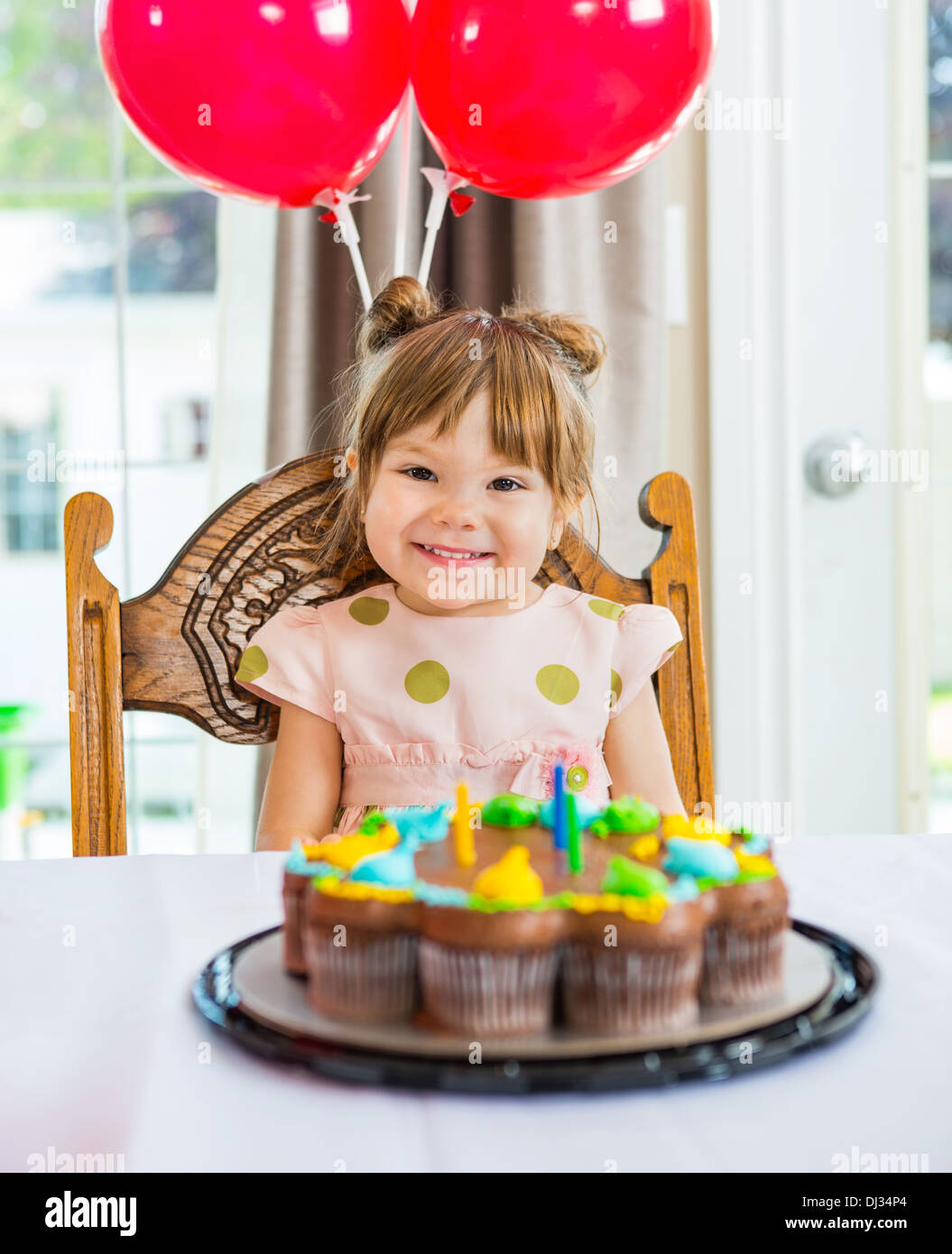 Happy Girl Sitting In Front Of Cake At Home - Stock Image