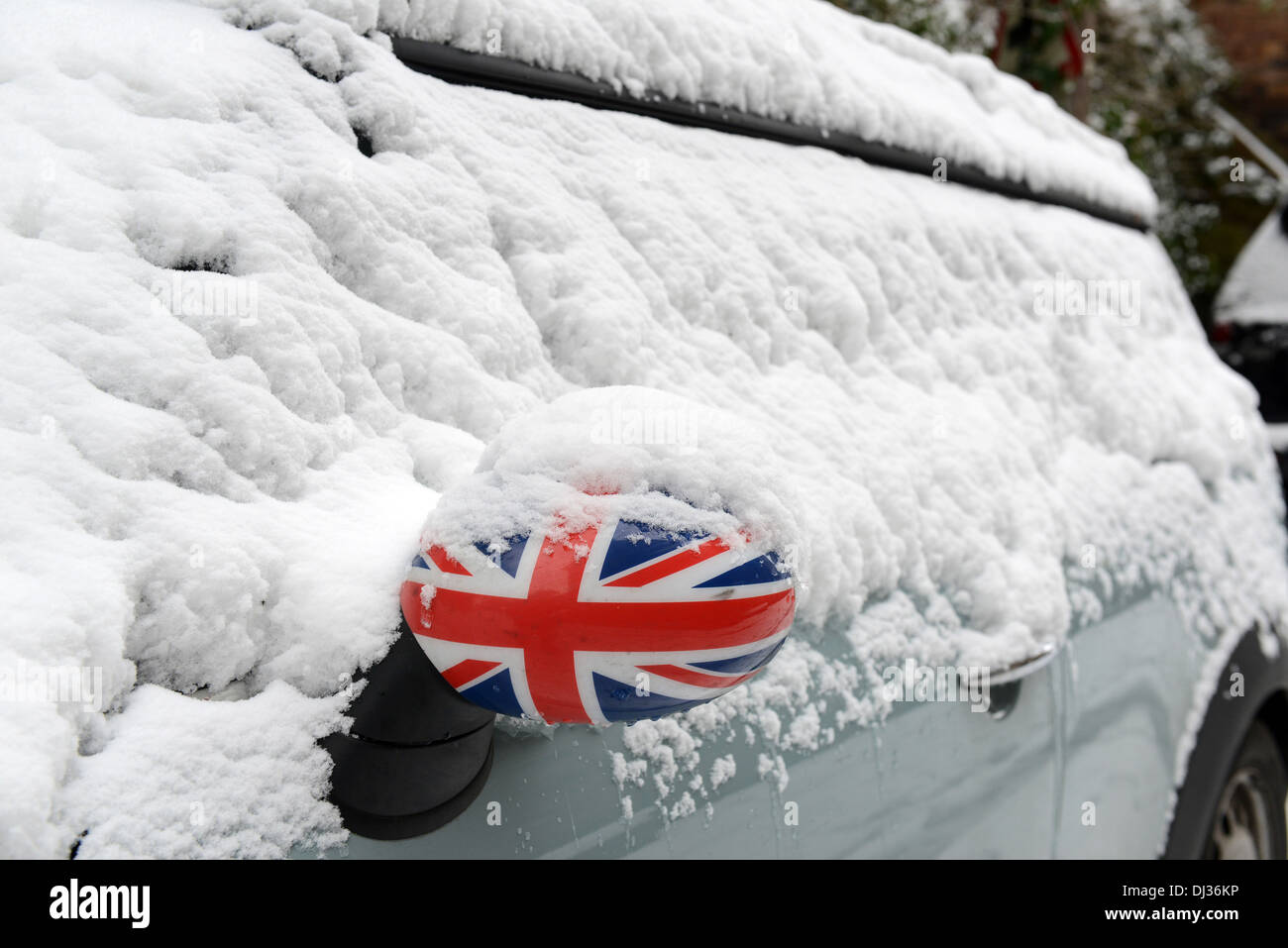 British winter weather snow covered Mini car with Union Jack wing mirror 2013 - Stock Image