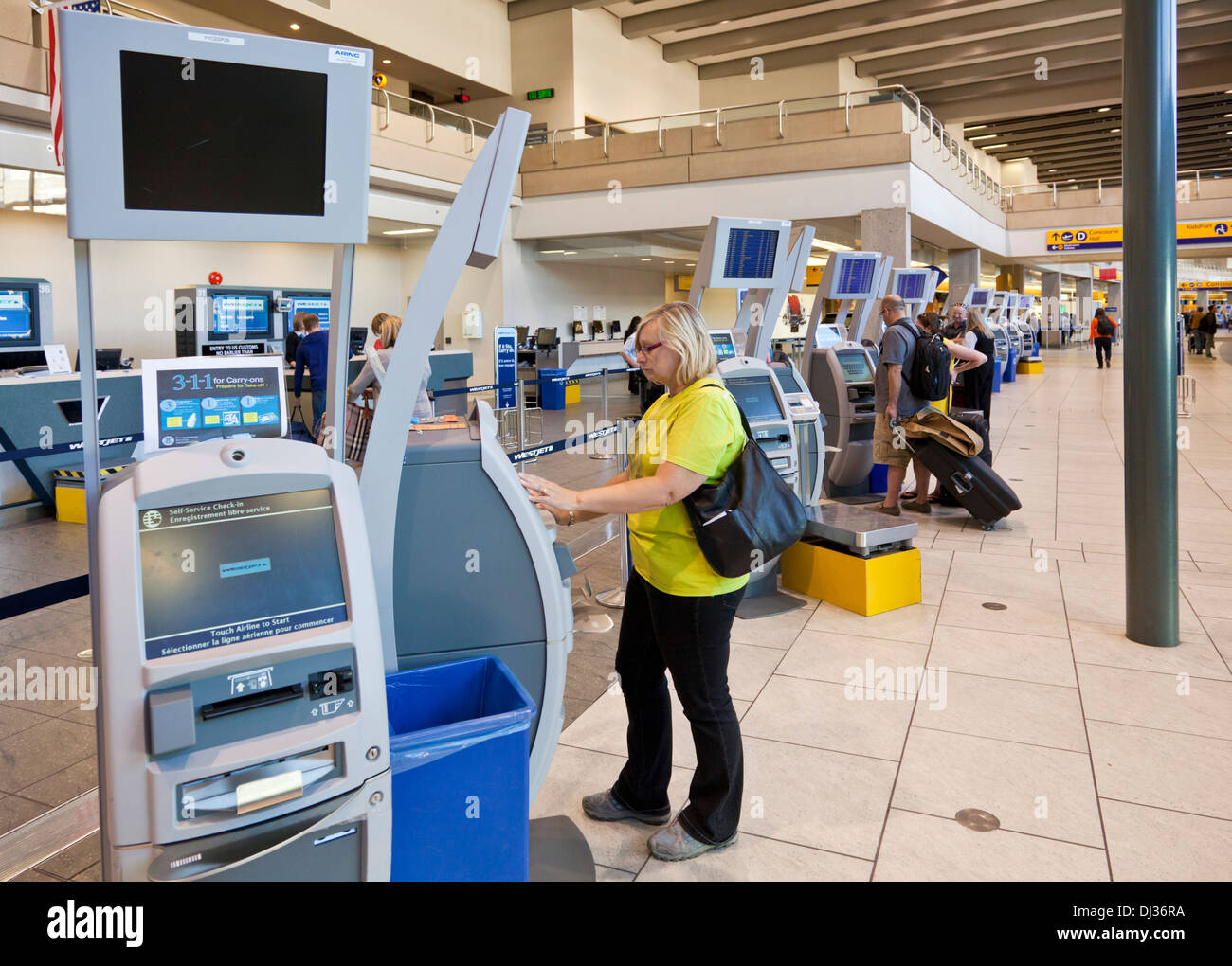 Calgary woman using automatic check in machines airport departures hall Calgary International Airport Alberta Canada - Stock Image