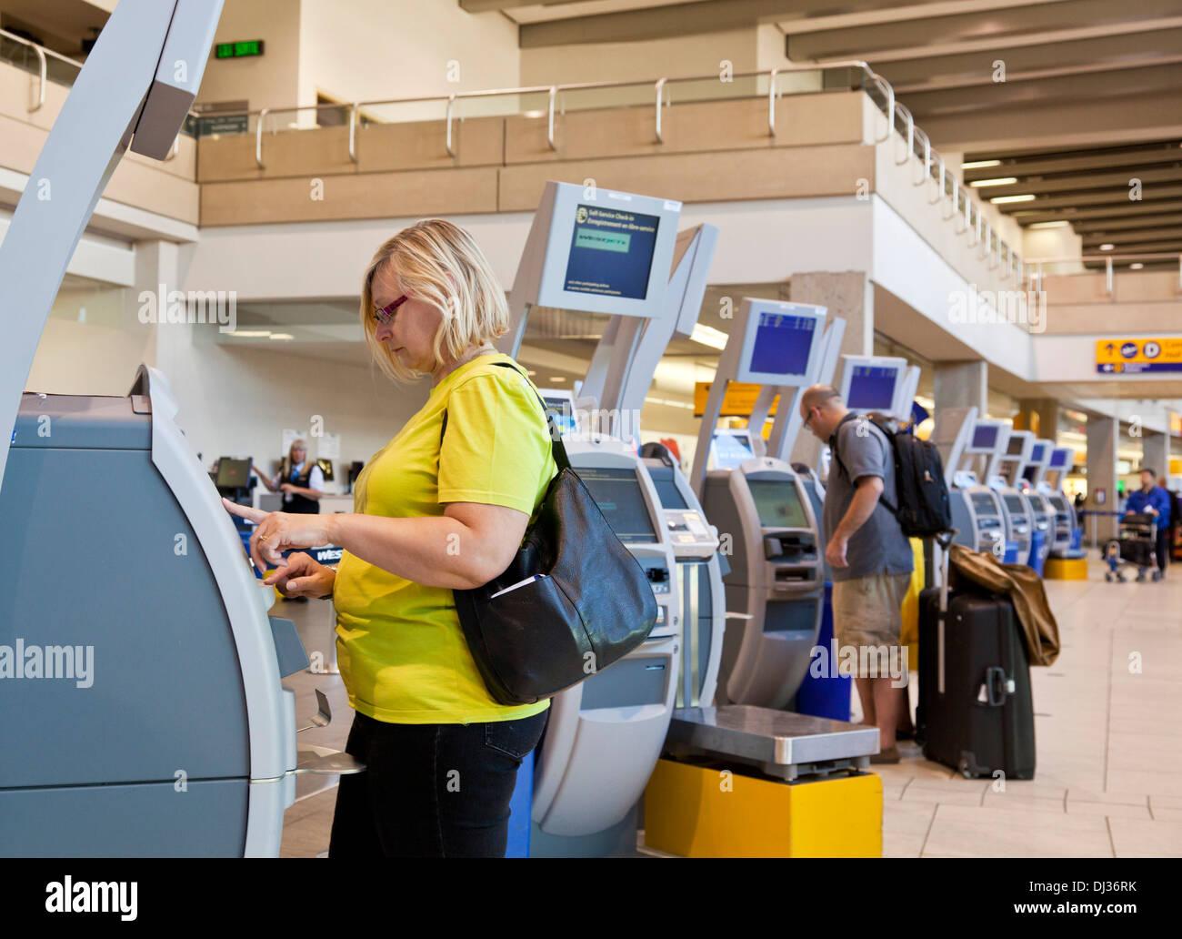 Calgary International Airport woman using automatic check in machines airport departures Calgary Alberta Canada - Stock Image