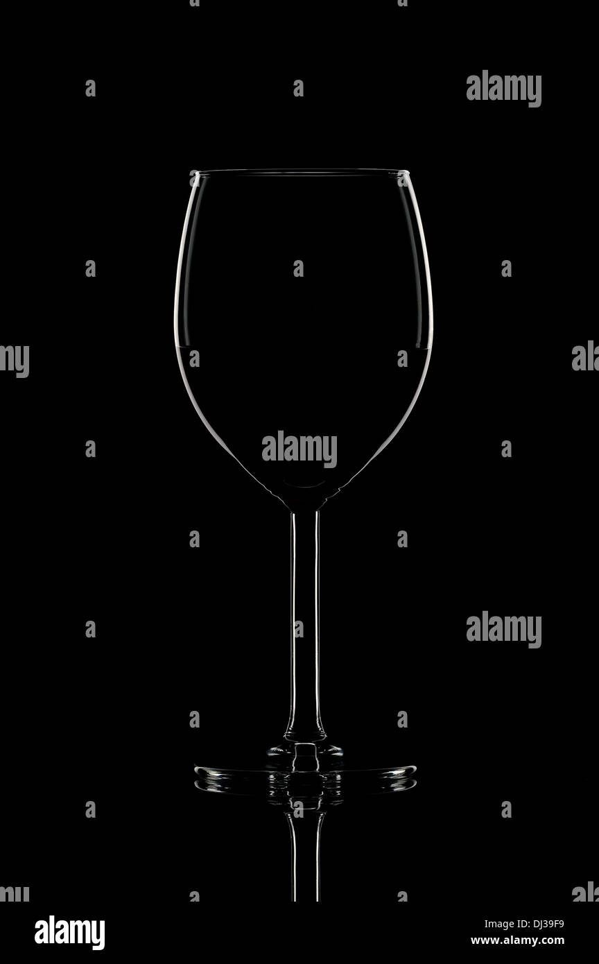 One elegant wine glass with red wine on shine black background with reflection. Light contour. - Stock Image