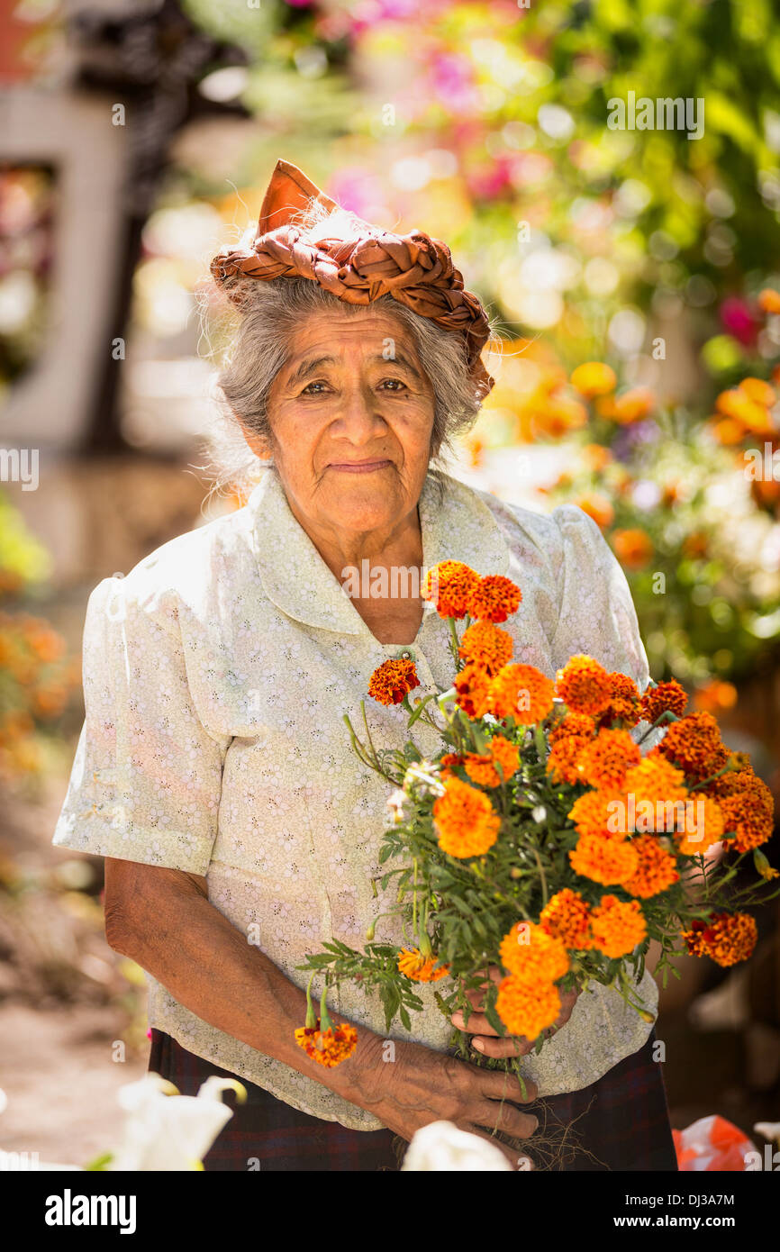 An elderly Zapotec woman smiles as she places fresh flowers on the grave of a family member for the Day of the Dead festival. - Stock Image