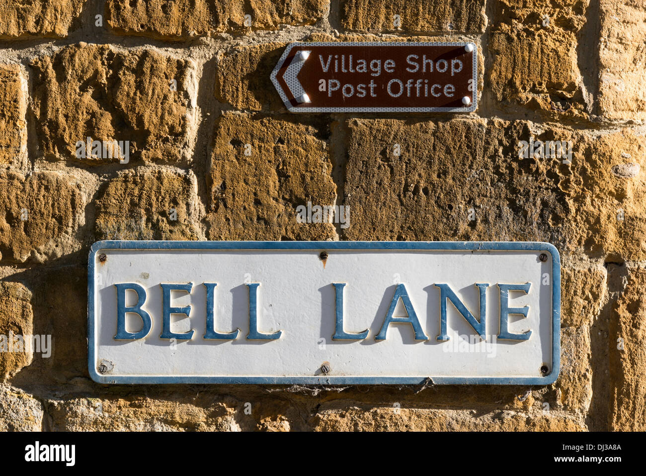Road name sign and direction sign to the village shop and post office on a cotswold limestone wall in Blockley The cotswolds UK - Stock Image
