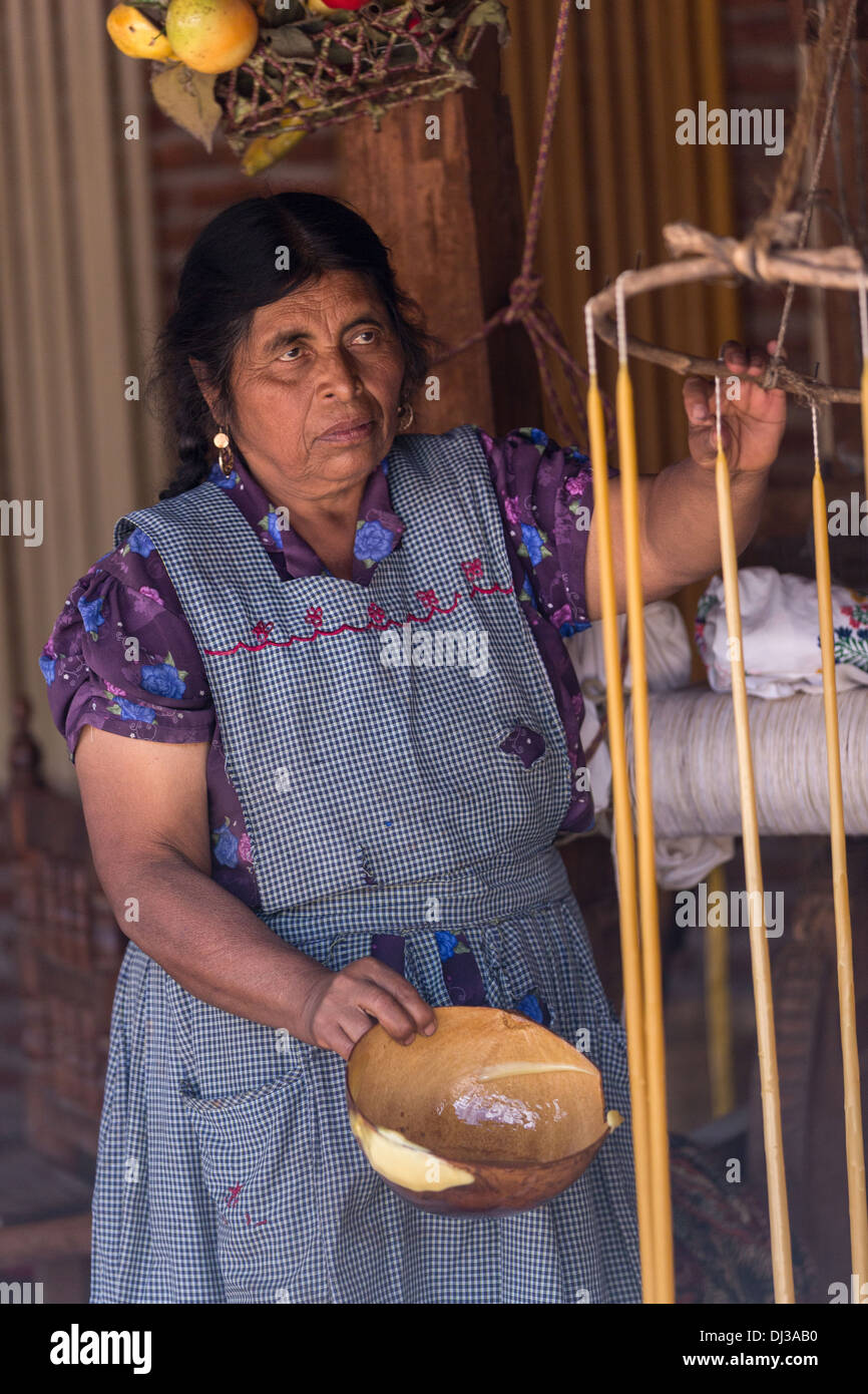 A Zapotec indigenous woman hand makes beeswax candles for the Day of the Dead festival in Teotitlan, Mexico. - Stock Image