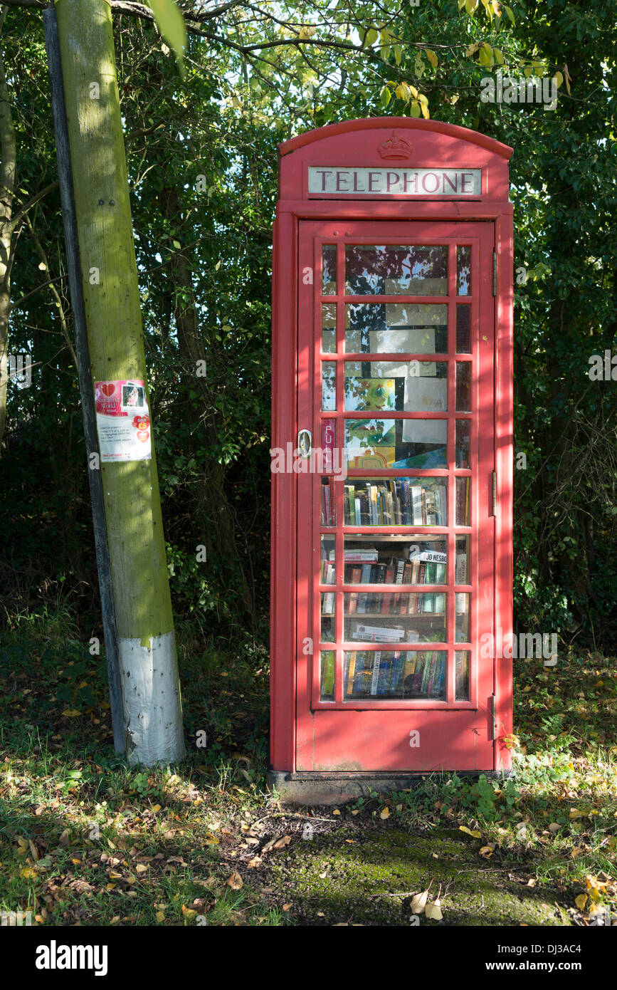 A traditional English red telephone box transformed into a village library for storing reusable books. - Stock Image
