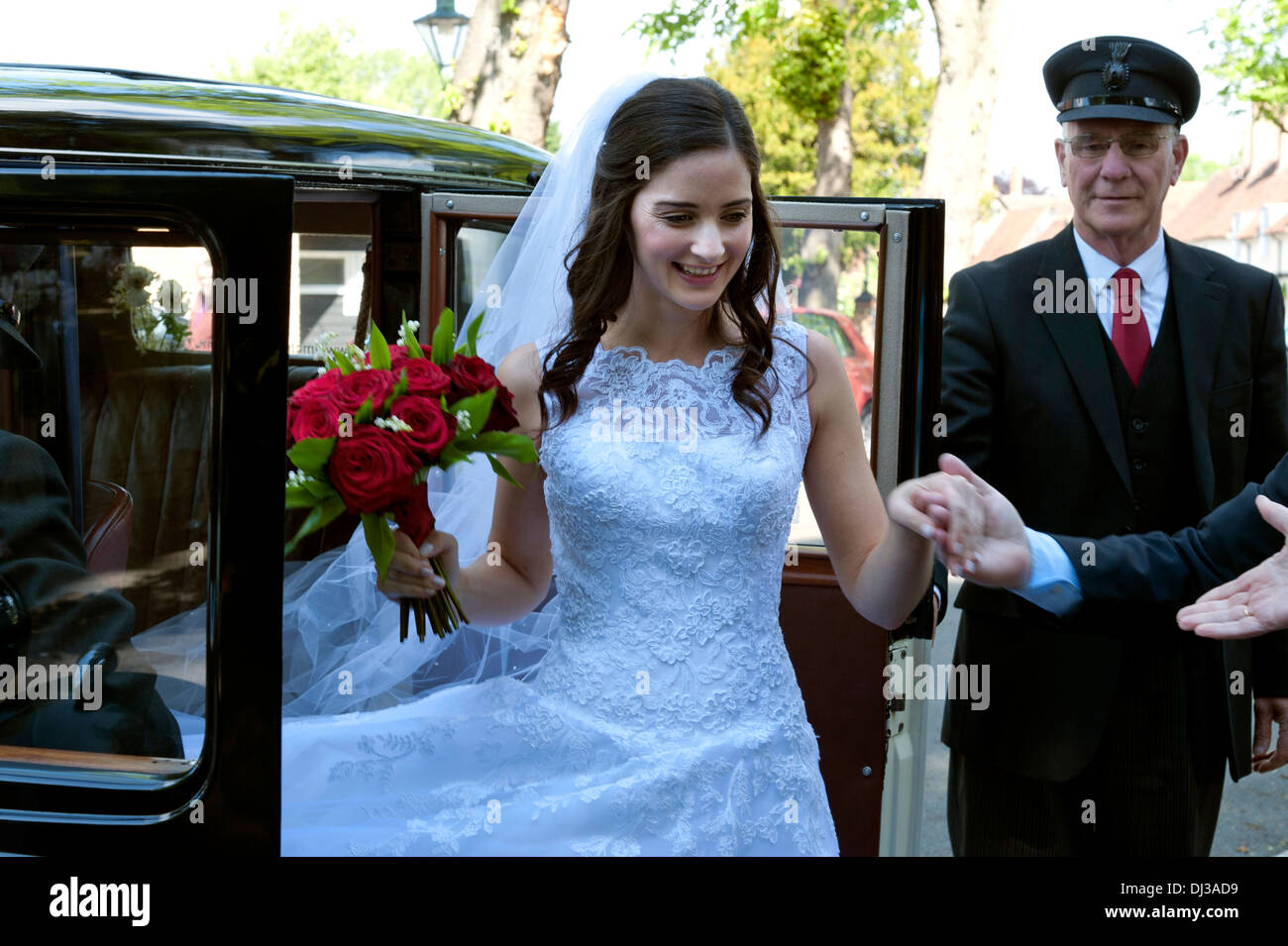 Bride Arriving In Traditional White Wedding Dress Carrying Bouquet
