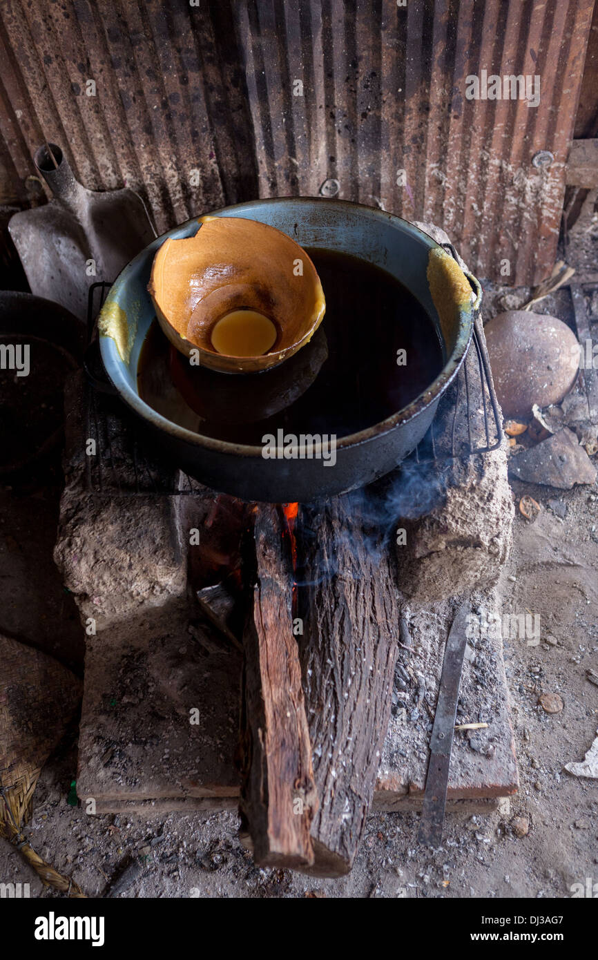 Beeswax is melted on a fire for making candles in preparation for the Day of the Dead festival in Teotitlan, Mexico. - Stock Image