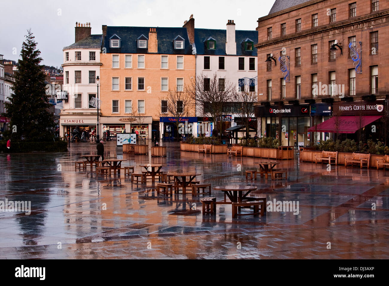 Reflections of the Christmas Tree and buildings along the City Square after a passing rain shower in Dundee, UK - Stock Image