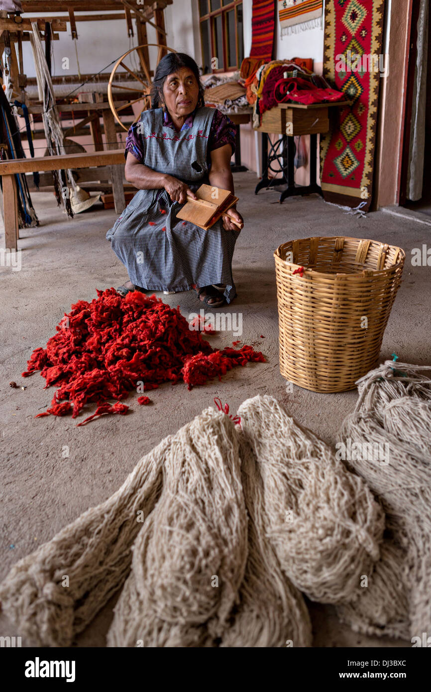 A Zapotec indigenous woman hand cards dyed wool into yarn to be used in weaving traditional carpet in Teotitlan de Valle, Mexico - Stock Image