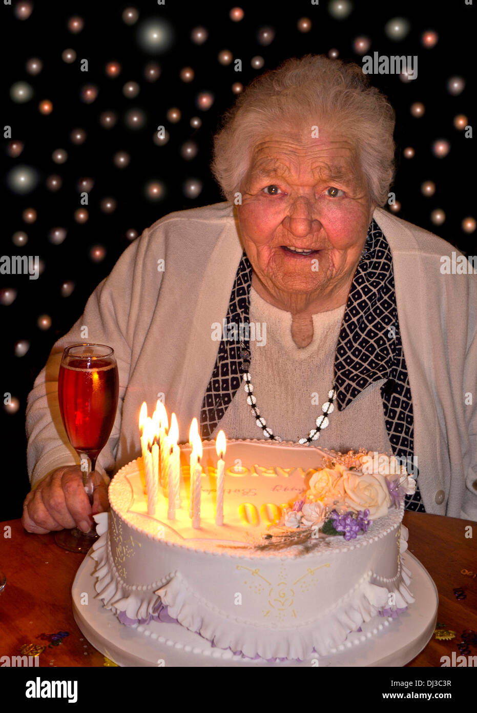Happy Alert Elderly Lady At 100 Years Of Age With Her Birthday Cake And A Glass
