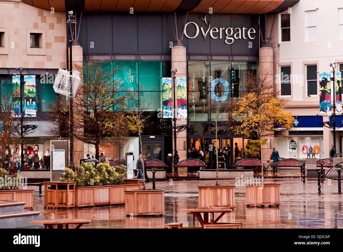 Shoppers standing at the entrance of the Overgate Shopping Centre sheltering from the November Rain Showers in Dundee, Stock Photo