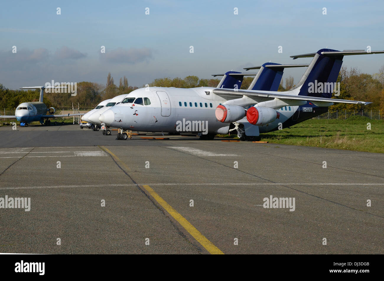 A number of aircraft in storage at Southend Airport, with fire and evacuation trainer aircraft in the background. 'Graveyard' - Stock Image