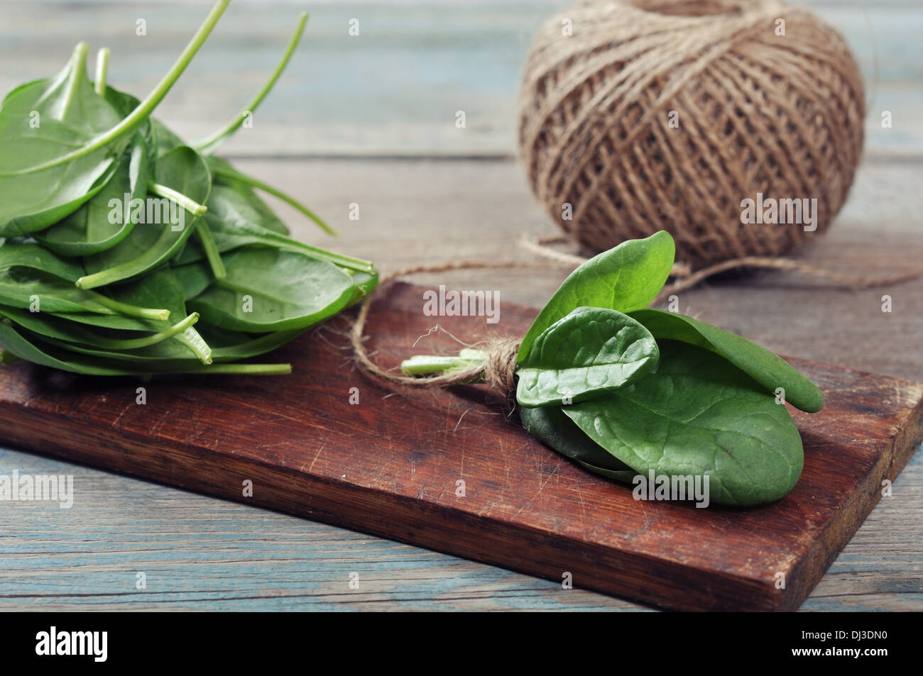 Fresh spinach leaves on wooden cutting board closeup - Stock Image