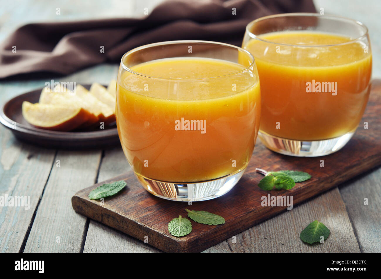 Mango smoothie in glass with mint on wooden background - Stock Image
