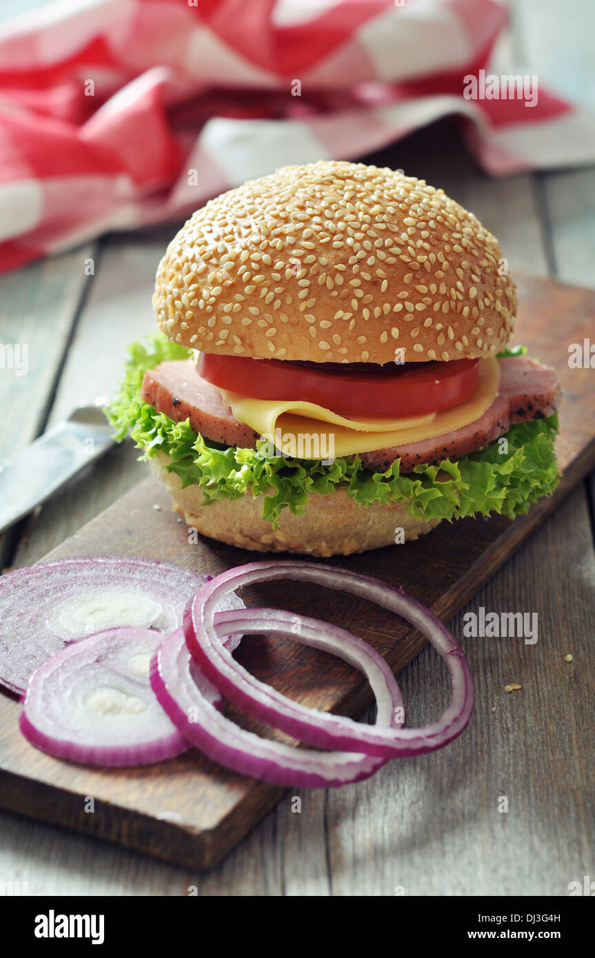 Sandwich with ham, cheese, tomato and lettuce on wooden cutting board closeup - Stock Image
