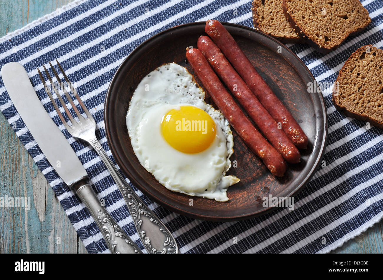 Fried egg with sausages on plate over wooden background - Stock Image